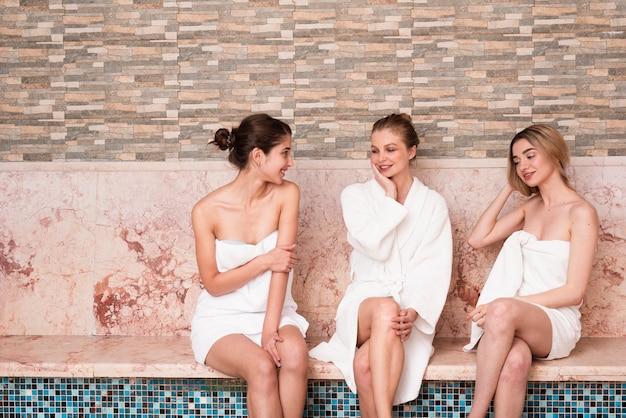 Gruppo di amici in chat a bordo piscina presso spa