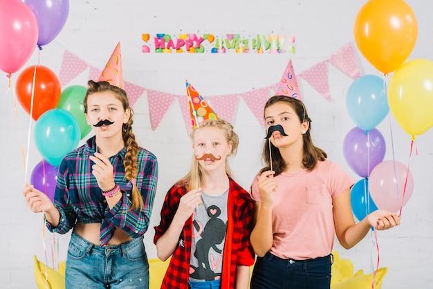 Gruppo di amici in posa con i baffi di puntello durante il compleanno