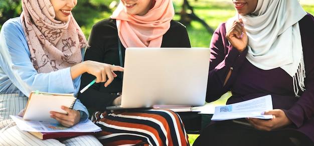 Gruppo di amici islamici, discutendo e lavorando insieme