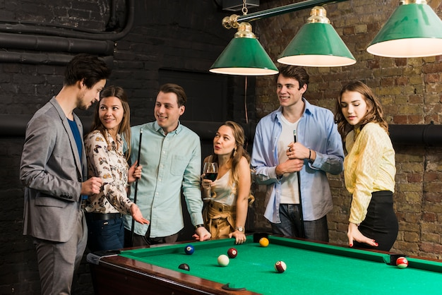 Gruppo di amici maschi e femminili in piedi al tavolo da biliardo