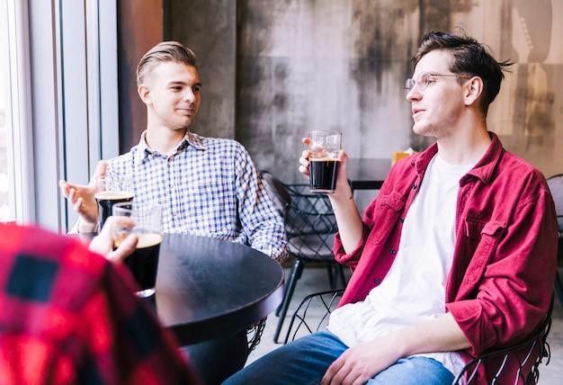 Gruppo di amici maschi godendo la birra nel ristorante