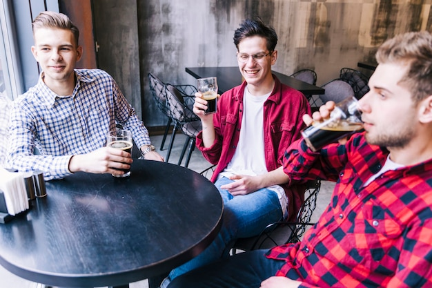 Gruppo di amici maschi seduti insieme a tavola godendo la birra nel ristorante bar