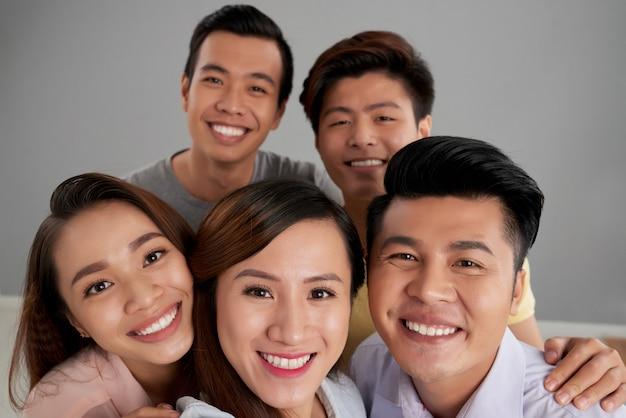 Gruppo di amici maschii e femminili asiatici che posano insieme