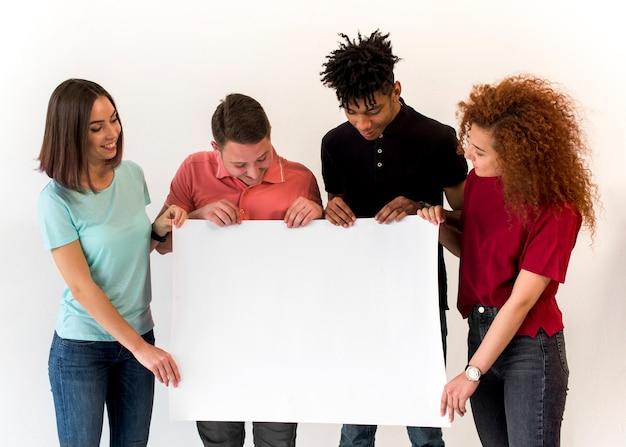 Gruppo di amici multietnici sorridenti che tengono cartello bianco in bianco che sta nel fondo bianco