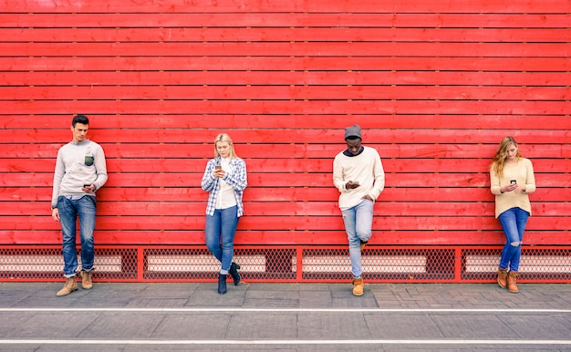 Gruppo di amici multirazziali di moda che per mezzo dello smartphone con la parete di legno rossa