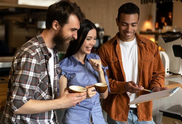 Gruppo di amici multirazziali felici che bevono caffè in caffè, comunicazione, parlare. hipsters sorridenti progetto di lavoro, cooperazione, lavoro di squadra