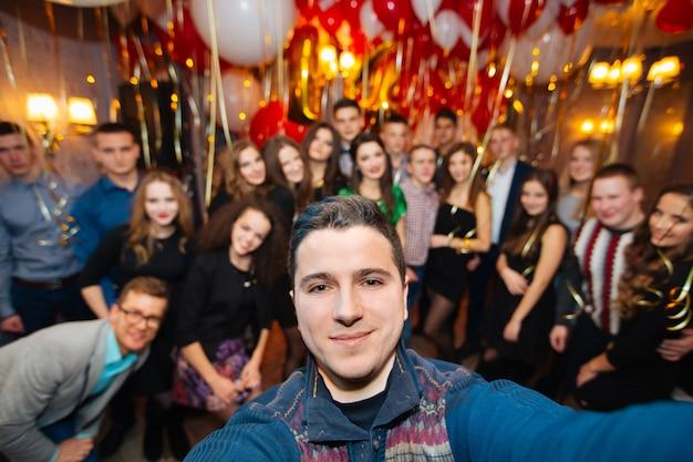 Gruppo di amici nel club che fanno selfie e si divertono, festa di compleanno