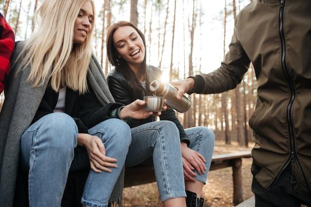Gruppo di amici seduti all'aperto nella foresta di bere il tè.