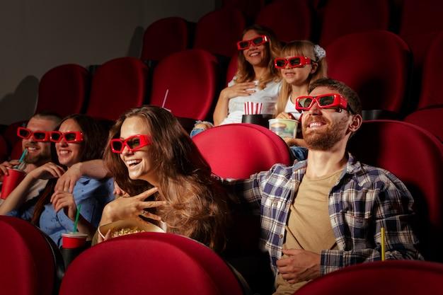 Gruppo di amici seduti nel cinema con popcorn e bevande