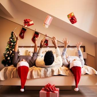 Gruppo di amici sono sdraiati a letto e lanciano regali in aria per le vacanze di natale.