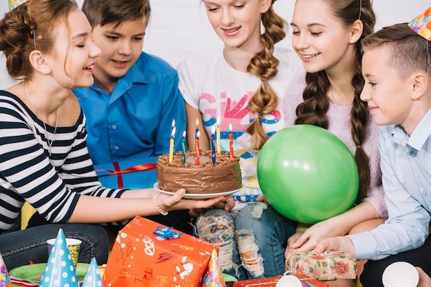 Gruppo di amici sorridenti che esaminano la torta di compleanno con le candele illuminate