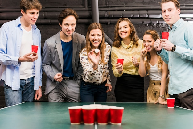 Gruppo di amici sorridenti felici che godono del gioco del pong della birra sulla tavola nella barra