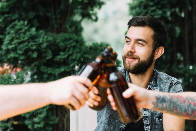 Gruppo di amici tintinnano le bottiglie di birra all'aperto