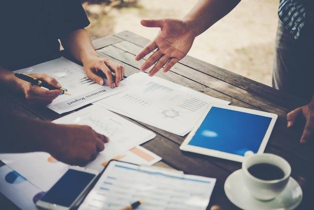 Gruppo di analisti di business people con grafico di report marketing, giovani specialisti stanno discutendo idee di business per il nuovo progetto di avviamento digitale.