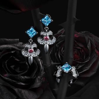 Gruppo di anelli e orecchini di oro bianco con topazio, granati e diamanti sul fondo nero delle rose naturali, percorso di ritaglio incluso.