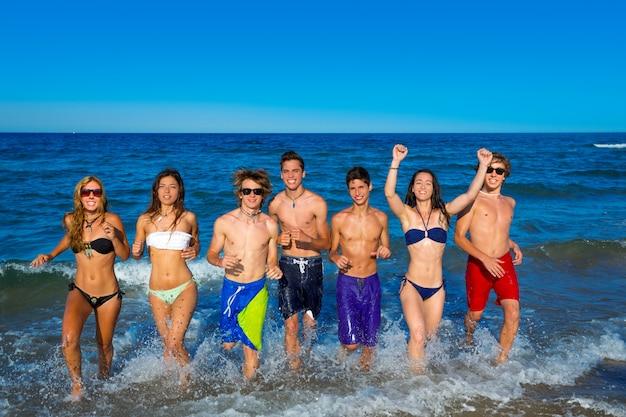 Gruppo di anni dell'adolescenza che corre felice che spruzza sulla spiaggia