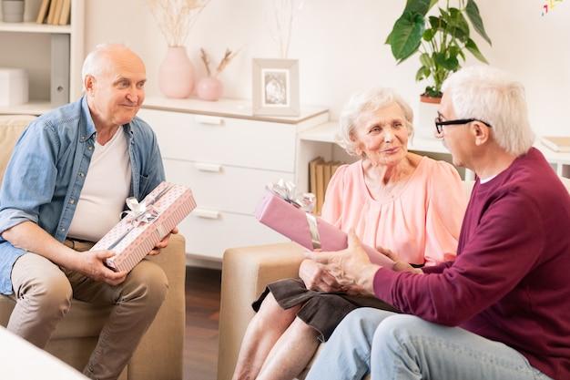 Gruppo di anziani allegri amichevoli seduti a casa mentre si gode la festa e si fanno regali a vicenda