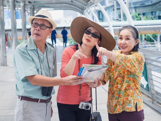 Gruppo di anziani che cammina in città, uomo anziano e donna guardando la mappa