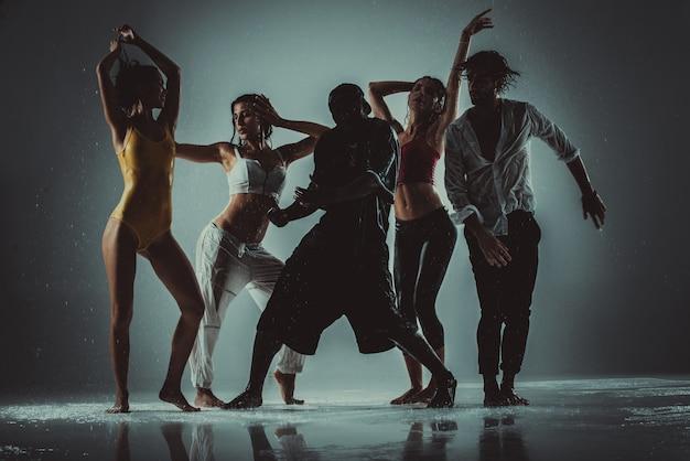 Gruppo di ballerini che ballano sul palco con effetto pioggia