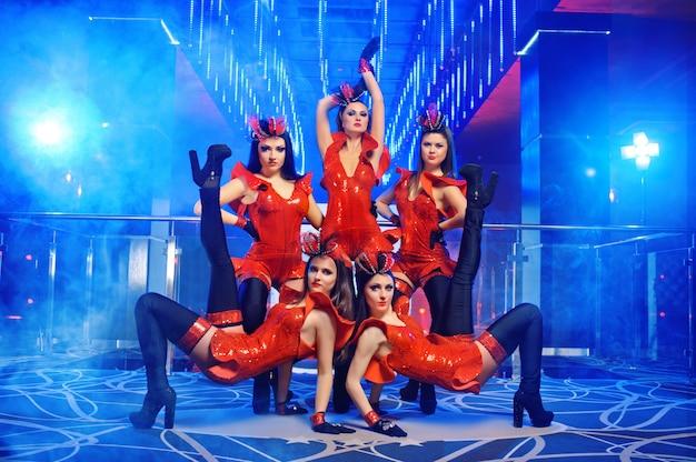 Gruppo di ballerini femminili sexy nell'esecuzione abbinata rossa degli abiti