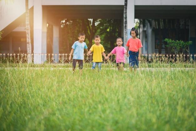 Gruppo di bambini asiatici che si tengono per mano e che corrono o che camminano insieme sul campo di erba alla scuola
