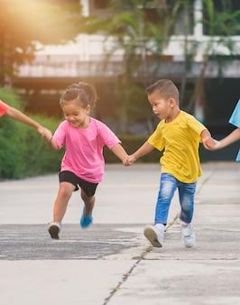 Gruppo di bambini asiatici che si tengono per mano e che corrono o che camminano insieme sul passaggio pedonale alla scuola