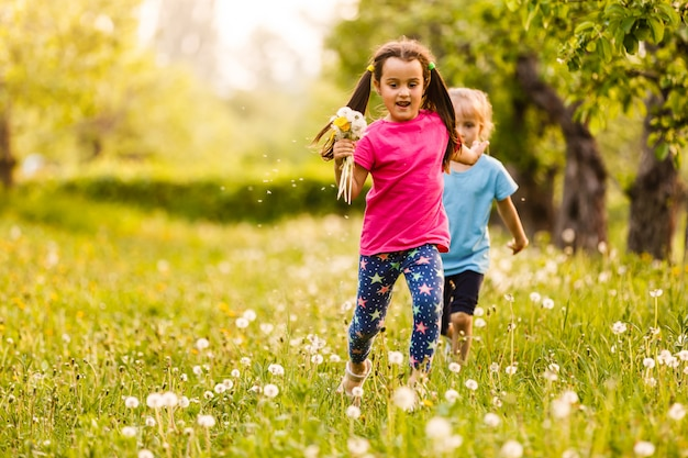 Gruppo di bambini che corrono nel campo di primavera tarassaco