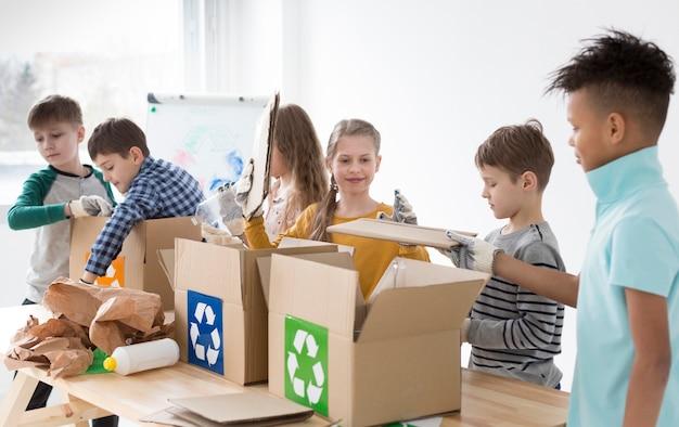 Gruppo di bambini che imparano a riciclare