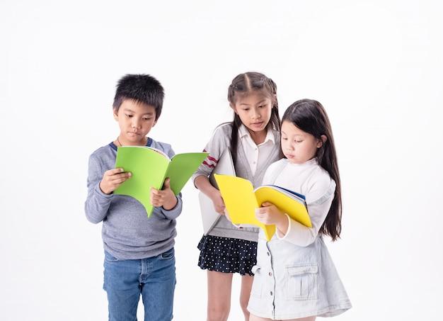 Gruppo di bambini che leggono un libro insieme, con sentimenti interessati, facendo attività insieme