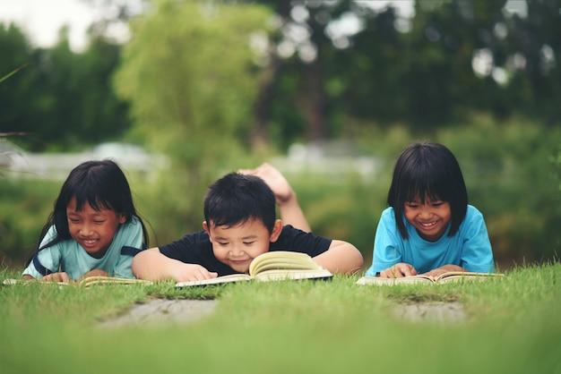 Gruppo di bambini che si trovano leggendo sul campo di erba