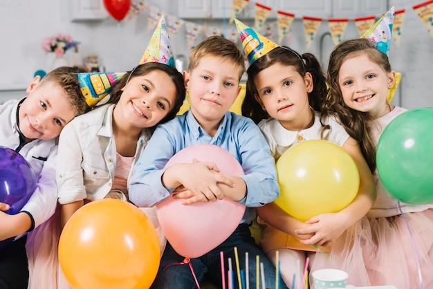 Gruppo di bambini che tengono palloncini colorati durante il compleanno