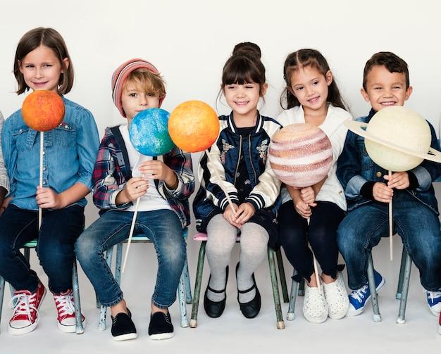 Gruppo di bambini che tengono simbolo della galassia di papercraft su blackground bianco