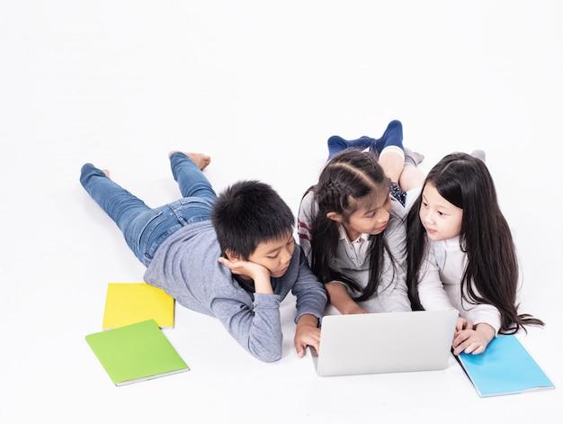 Gruppo di bambini che usano il portatile per l'apprendimento, facendo attività insieme, con sentimento interessato