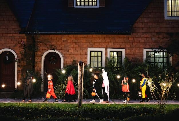 Gruppo di bambini con costumi di halloween che camminano per ingannare o trattare