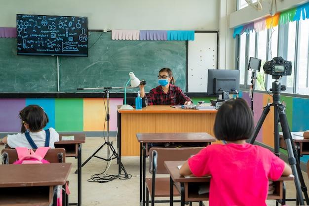 Gruppo di bambini della scuola con l'insegnante che si siede nell'aula alla scuola elementare.