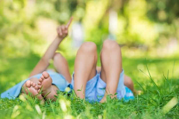 Gruppo di bambini felici che si trovano sull'erba verde