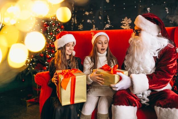 Gruppo di bambini seduti con santa e regali alla vigilia di natale
