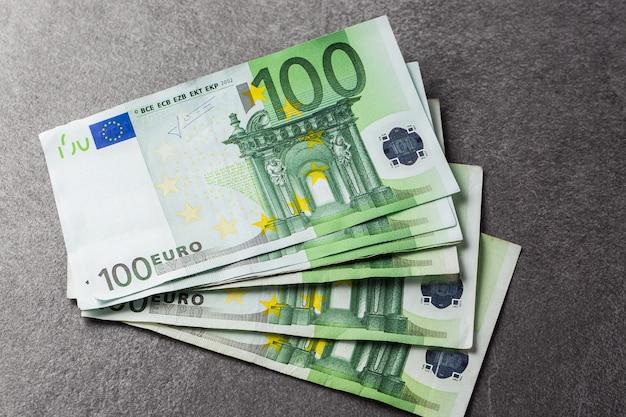 Gruppo di banconote da 100 euro. le banconote in euro si chiudono. diverse centinaia di banconote in euro molte delle cento banconote in euro si trovano fianco a fianco. concetto di ricchezza e investimenti sul grigio