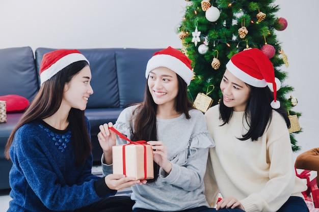 Gruppo di bei contenitori di regalo asiatici della tenuta della donna. fronte sorridente nella sala con la decorazione dell'albero di natale per le vacanze