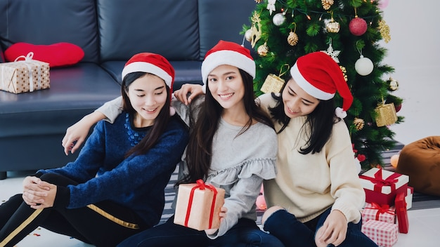 Gruppo di bei contenitori di regalo asiatici della tenuta della donna. fronte sorridente nella sala con la decorazione dell'albero di natale