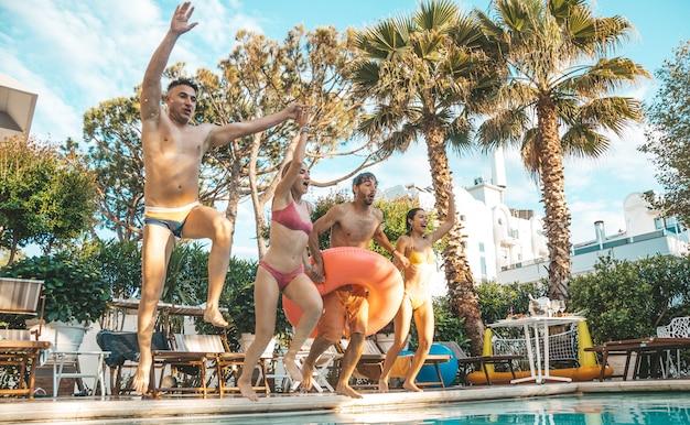Gruppo di bei giovani divertendosi saltando insieme nella piscina.