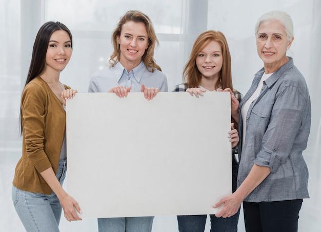 Gruppo di bella donna con un cartello