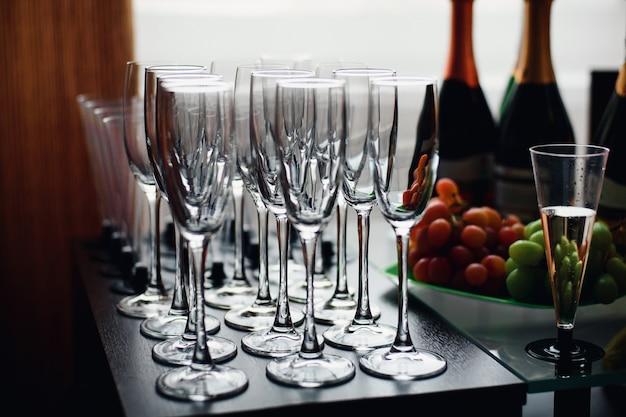 Gruppo di bicchieri di champagne per una vacanza con bottiglie e cibo al ristorante