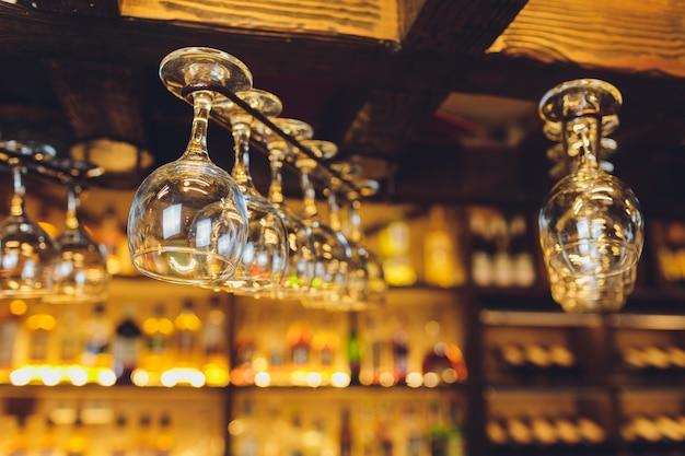 Gruppo di bicchieri di vino vuoti che pendono dalle travi di metallo in una barra.