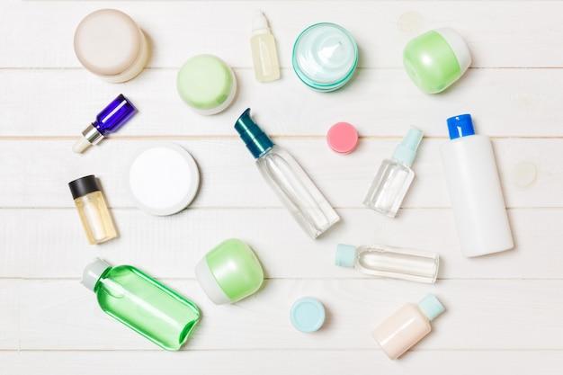 Gruppo di bottiglia di plastica bodycare composizione piatta laica con prodotti cosmetici su spazio vuoto in legno. set di contenitori cosmetici bianchi, vista dall'alto con copyspace