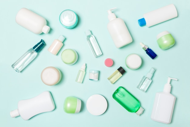 Gruppo di bottiglia di plastica per la cura del corpo composizione piatta laica con prodotti cosmetici su spazio vuoto blu per la progettazione. set di contenitori cosmetici bianchi, vista dall'alto con copyspace