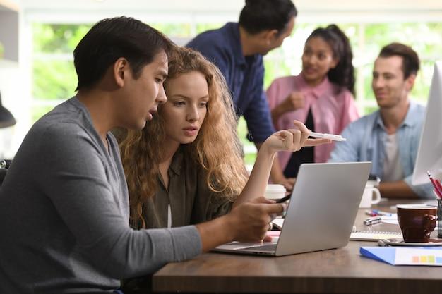 Gruppo di businesspersons in affari creativi che discutono di lavoro in ufficio