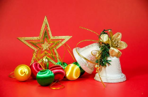 Gruppo di campana, palla e regalo di natale su sfondo rosso