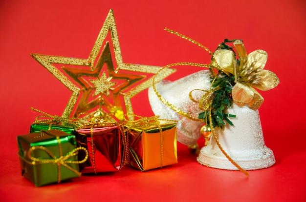 Gruppo di campana, regalo e stella nel natale su fondo rosso