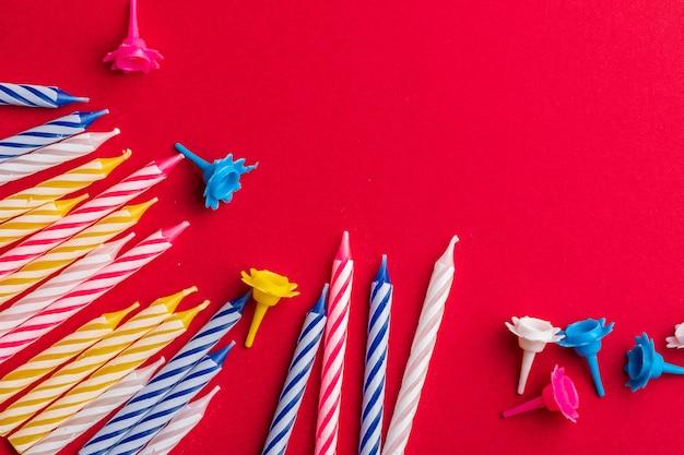 Gruppo di candele di compleanno su sfondo rosso. per auguri di compleanno. spazio per inserire testo. molto colorato, con blu, rosso, giallo e bianco.